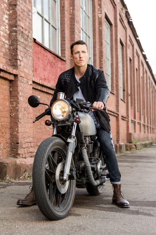 Brutalny mężczyzna siedzi na cukiernianym setkarza zwyczaju motocyklu zdjęcie royalty free