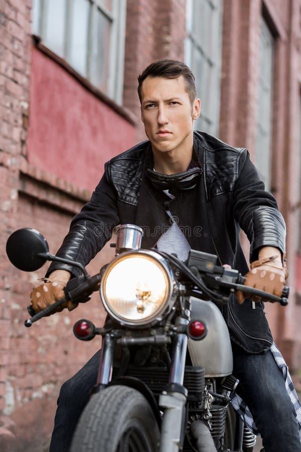 Brutalny mężczyzna siedzi na cukiernianym setkarza zwyczaju motocyklu obrazy royalty free