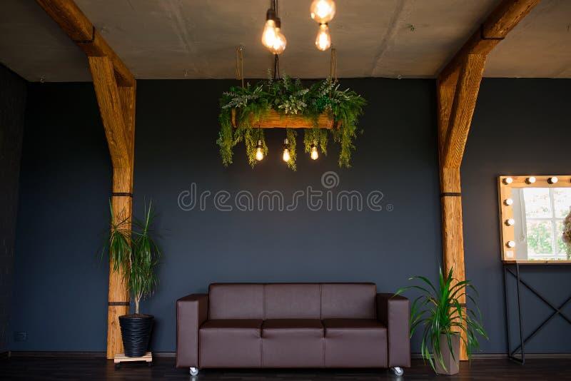 Brutalny nowożytny wnętrze w ciemnym kolorze z rzemienną kanapą Loft stylowy ?ywy pok?j obraz stock