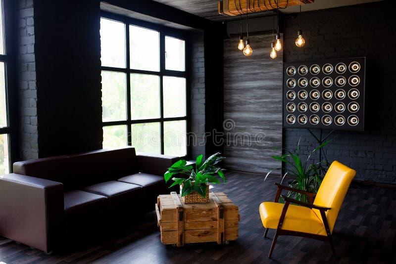 Brutalny nowożytny wnętrze w ciemnym kolorze z rzemiennym ampuły okno i kanapą Loft stylowy ?ywy pok?j fotografia royalty free