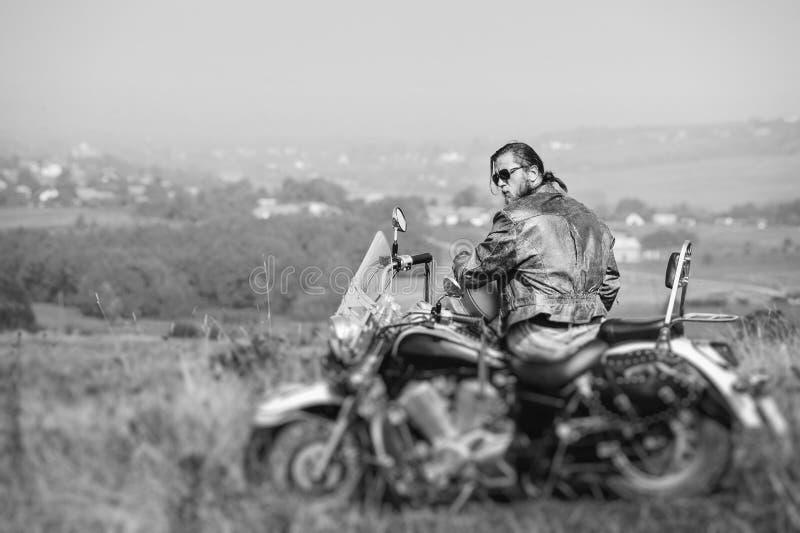 Brutalt cyklistsammanträde på hans motorcykel på en solig dag arkivfoton