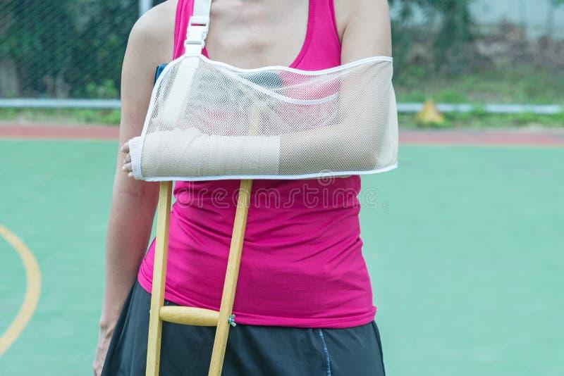 Bruten arm för sårad kvinna och hållande krycka för ben royaltyfri bild