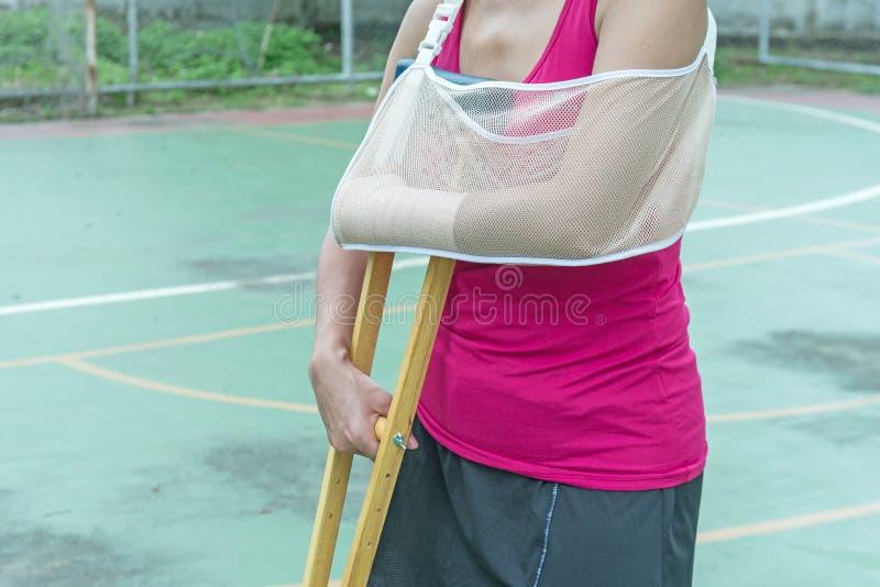 Bruten arm för sårad kvinna och hållande krycka för ben royaltyfri foto