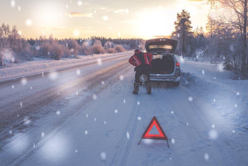 Bruten bil på en snöig vinterväg arkivbilder
