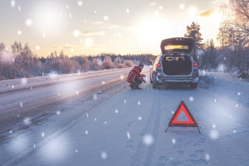 Bruten bil på en snöig vinterväg royaltyfria foton