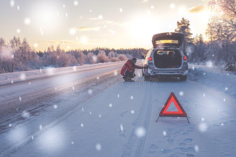 Bruten bil på en snöig vinterväg arkivbild