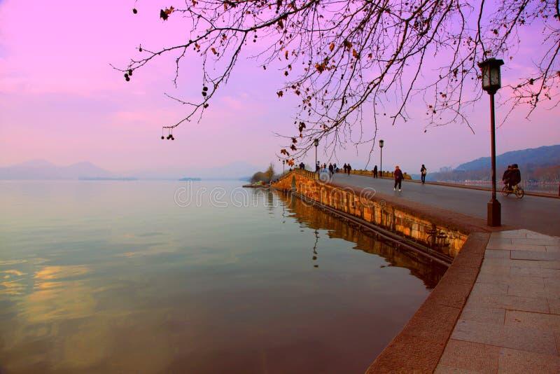 Bruten bro västra sjö Kina på solnedgången royaltyfri bild