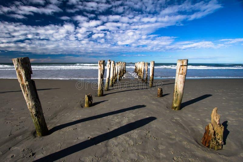 Bruten brygga som ut ser till gamla Pilings för hav som lämnas i sand royaltyfri foto
