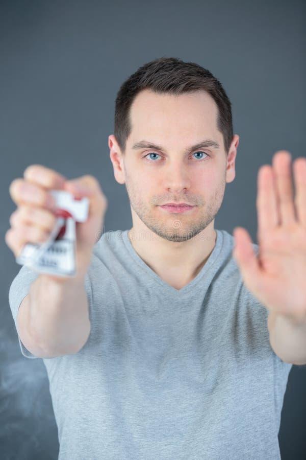 Bruten cigarettpacke i handen som isoleras på vit bakgrund arkivfoton