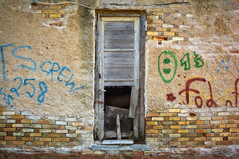 Bruten dörr i en riden ut vägg arkivfoto