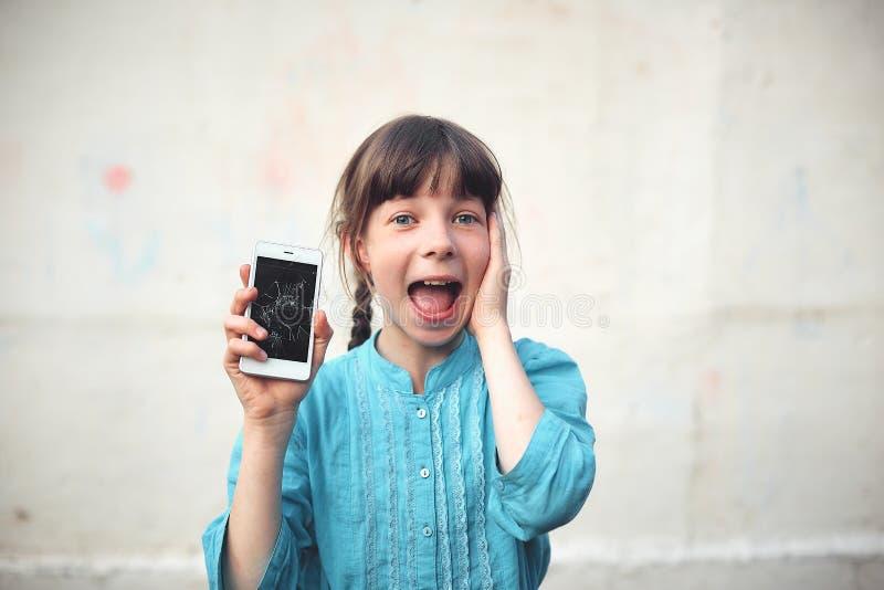 Bruten glass skärmsmartphone i hand av den upprivna flickan, vit bakgrund royaltyfri fotografi