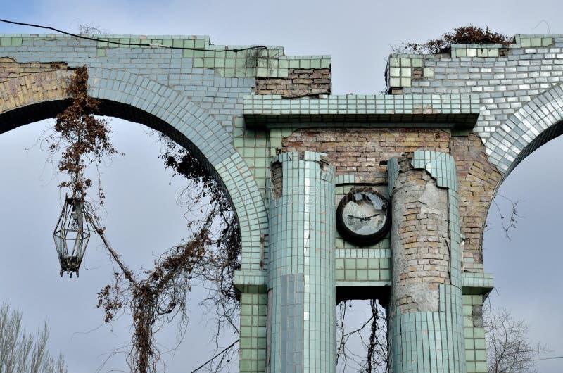 Bruten klocka och lykta på ingången av den förstörda gamla övergav iscensätta växten, Odessa, Ukraina arkivbilder