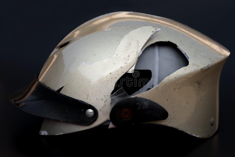 Bruten motobikehjälm på svart bakgrund arkivbild