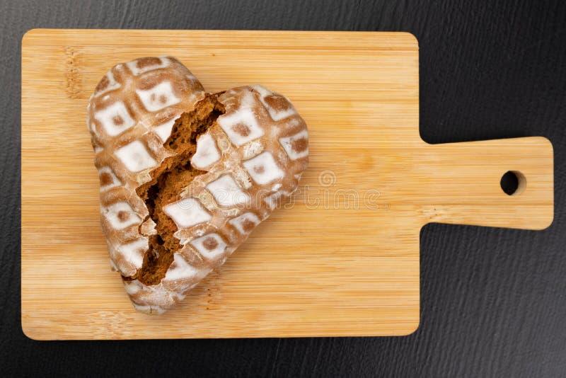 Bruten pepparkakahjärta på köksbordet Söta kakor dekoreras beautifully med isläggning royaltyfri fotografi