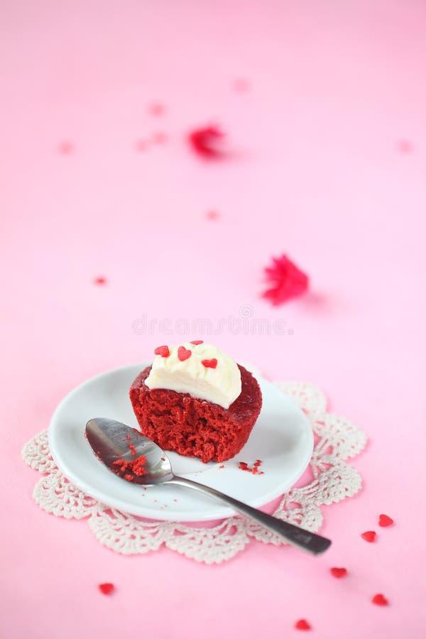 Bruten röd sammetmuffin med gräddostglasyr på kaka royaltyfri foto