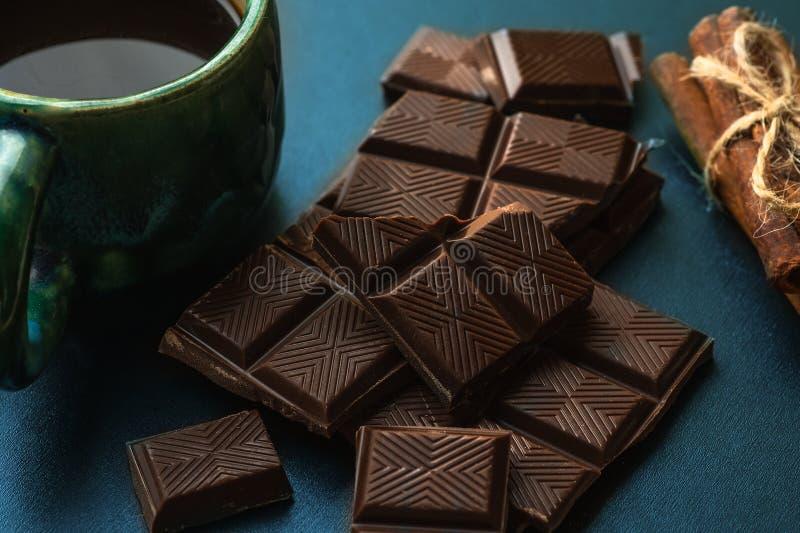 Bruten stång av choklad, kanel och koppen kaffe en svart tabell, slut upp fotografering för bildbyråer