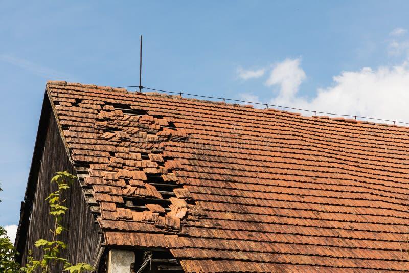 Bruten tegelsten hänger löst på taket av en stuga arkivfoton