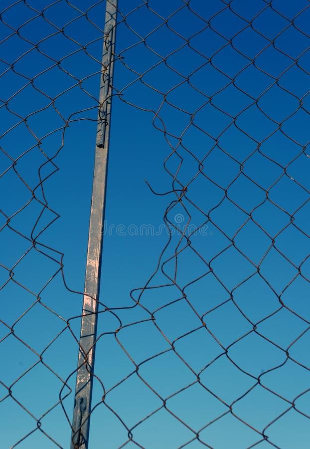 Bruten tråd Mesh Fencing med blå himmel royaltyfri bild