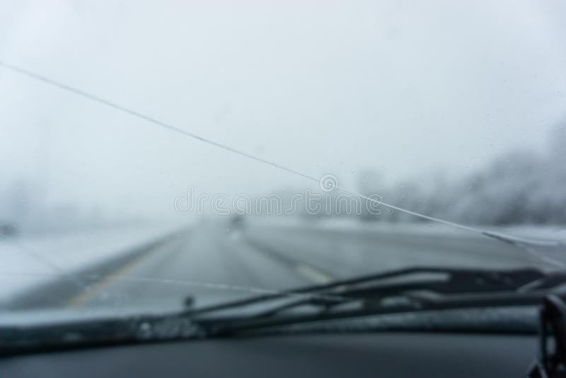 Bruten vindruta för vinterhuvudväg som ser på suddig vägplats arkivfoton