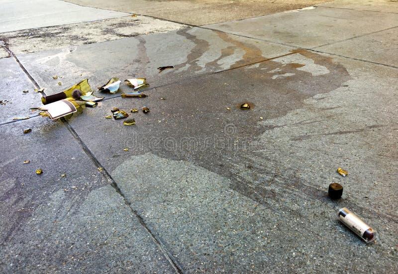 Bruten vinflaska och läppstift på konkret trottoar i staden arkivfoto