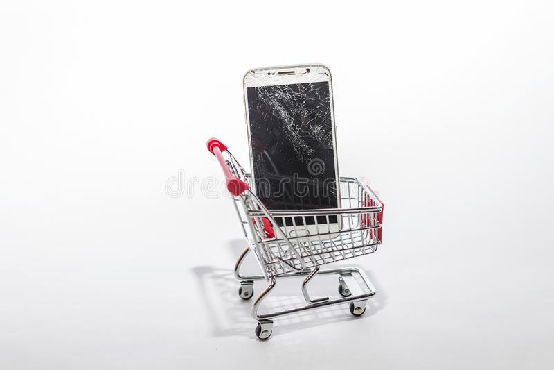 Bruten vit telefonskärm i shoppingvagn royaltyfri foto