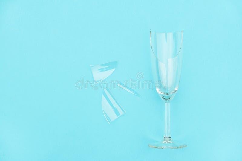 Brutet champagneexponeringsglas med splittrar på blå bakgrund med kopieringsutrymme Begreppskamp mot alkoholism, berusning och royaltyfri fotografi
