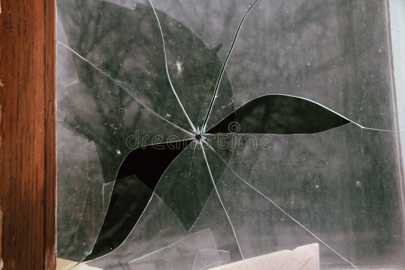 Brutet exponeringsglas med hålet från kula arkivfoto
