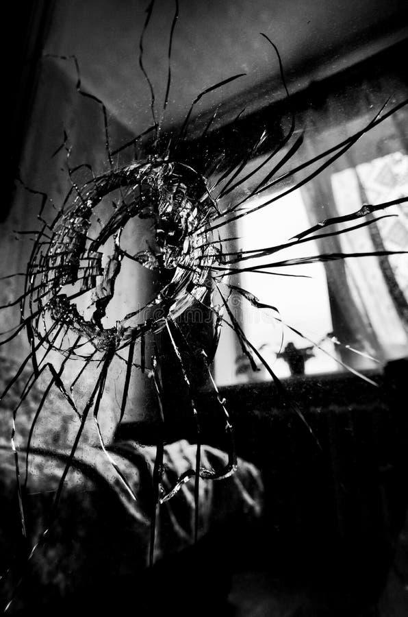 Brutet exponeringsglas med sprickor och en hål stiliserad svartvit film royaltyfria bilder