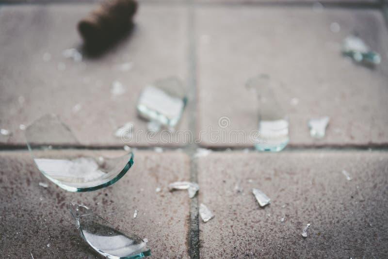 Brutet exponeringsglas på golvet, alkoholmissbruk royaltyfri foto