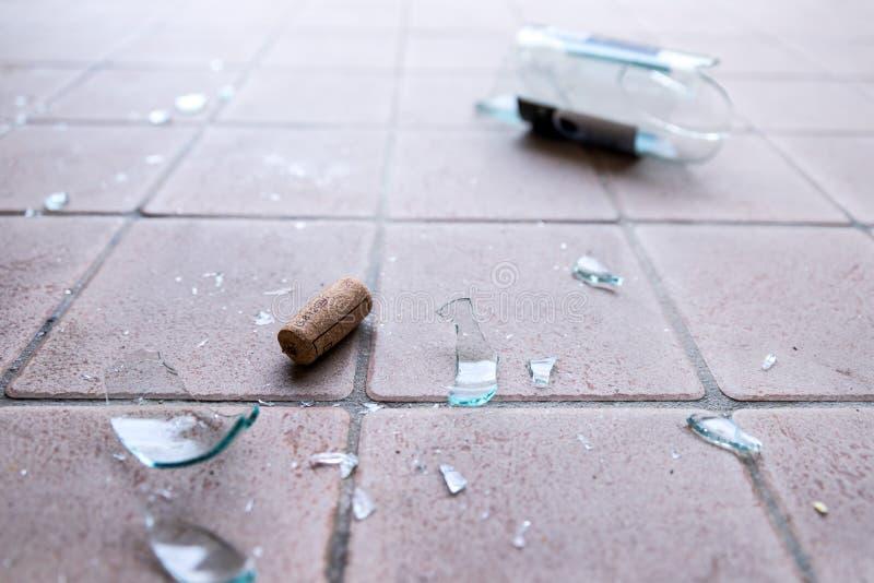 Brutet exponeringsglas på golvet, alkoholmissbruk royaltyfri bild