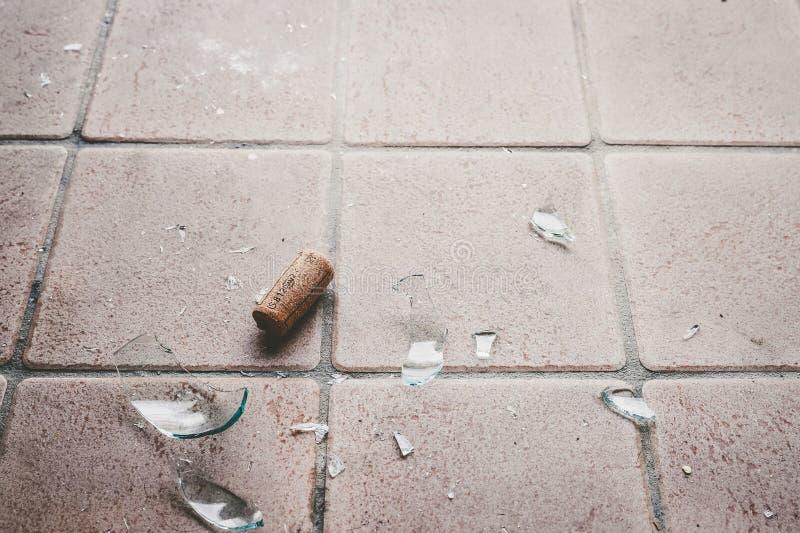 Brutet exponeringsglas på golvet, alkoholmissbruk arkivbilder