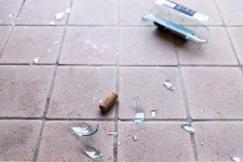 Brutet exponeringsglas på golvet, alkoholmissbruk arkivfoto