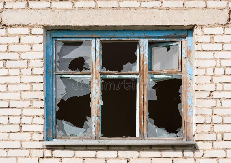 Brutet fönster i en tegelstenbyggnad royaltyfria foton
