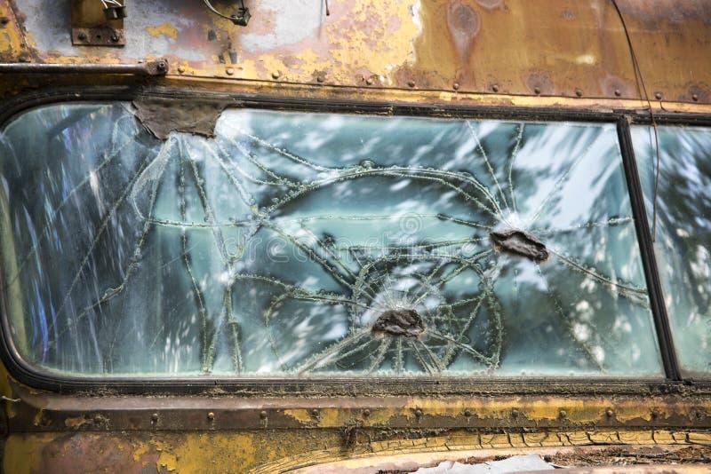 Brutet fönster i gammal skolbuss arkivbild