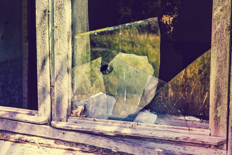 Brutet fönster med brutet exponeringsglas Kulhål i exponeringsglaset royaltyfri bild
