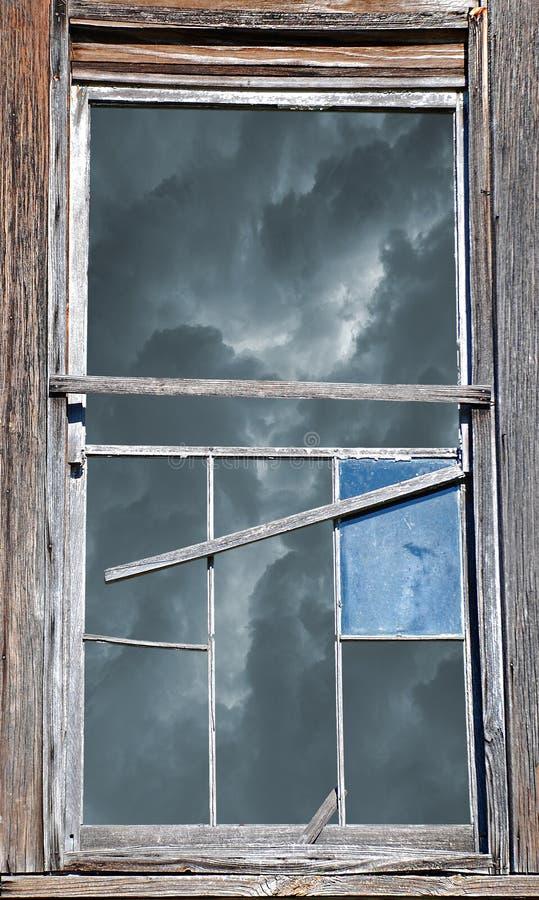 Brutet fönster med stormig himmel arkivbild