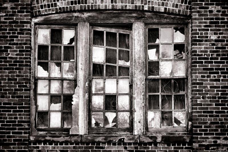 Brutet fönster på gammal övergiven industribyggnad royaltyfria foton