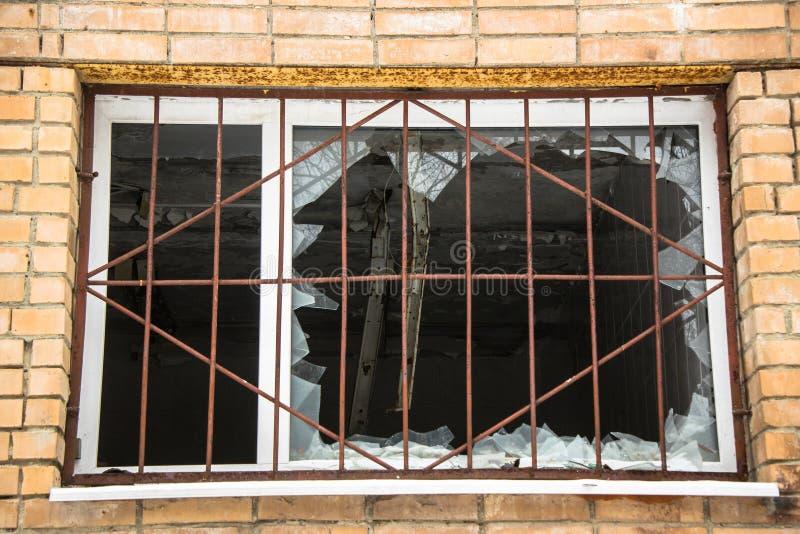Brutet gallerförsett fönster i ett övergett tegelstenhus Ligistfasoner vandalism royaltyfri bild
