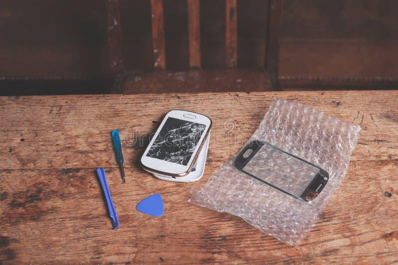Brutet ila telefonen och hjälpmedel arkivfoto