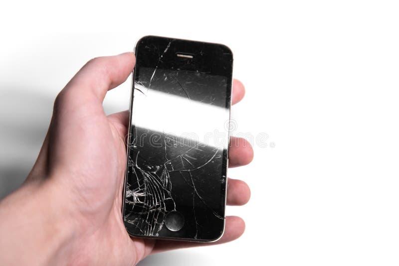 Brutet kraschat exponeringsglas på den smarta telefonen i hand på en vit bakgrund arkivbilder