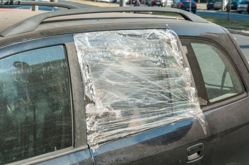 Brutet och skadat splittrat exponeringsglas av bilsidofönstret som skyddas med nylon, och kanalen som tejpas för att skydda inre  royaltyfri foto
