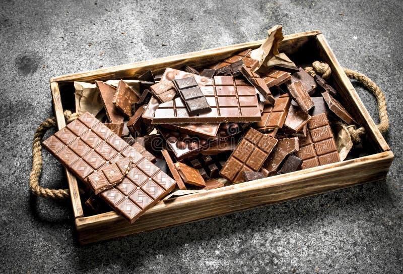 Brutna chokladstänger på trämagasinet arkivfoton