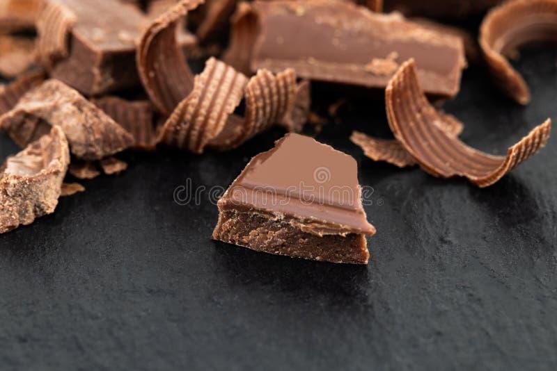 Brutna chokladstycken och chokladshavings på en mörk backgro arkivbilder