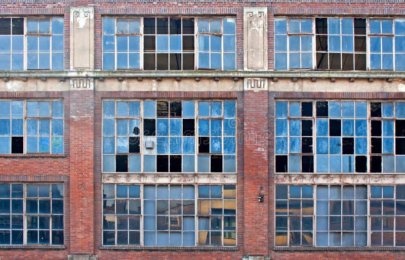 Brutna fönster på gammal övergiven byggnad royaltyfri foto