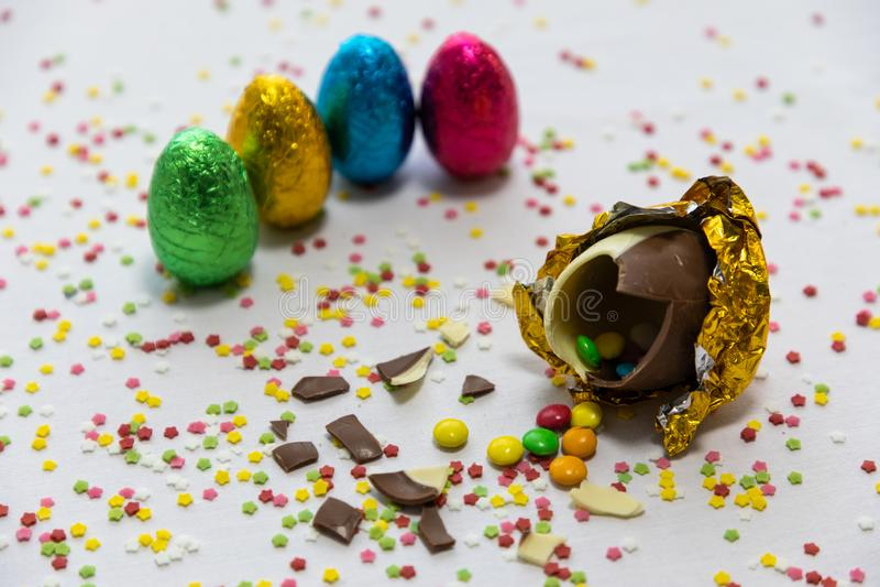 Brutna guld- chokladeaster ?gg med f?rgrika choklader inom p? vit bakgrund med f?rgrika suddiga konfettier och annan royaltyfri foto
