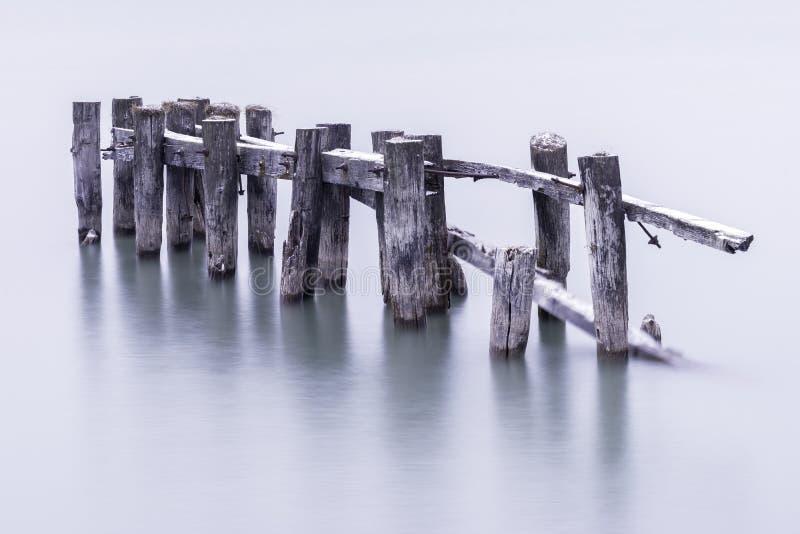 Brutna ner gamla pirstolpar i lugna vatten som är dolt med ljus dus royaltyfri foto