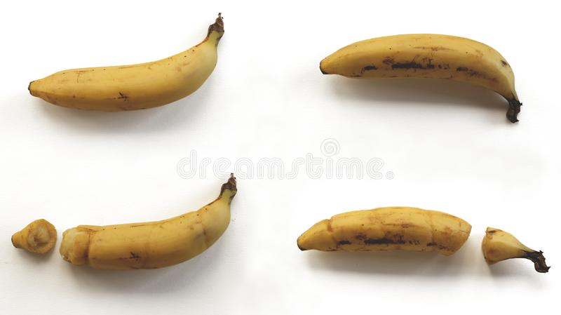 Brutna och intakta bananer på vit bakgrund arkivbilder