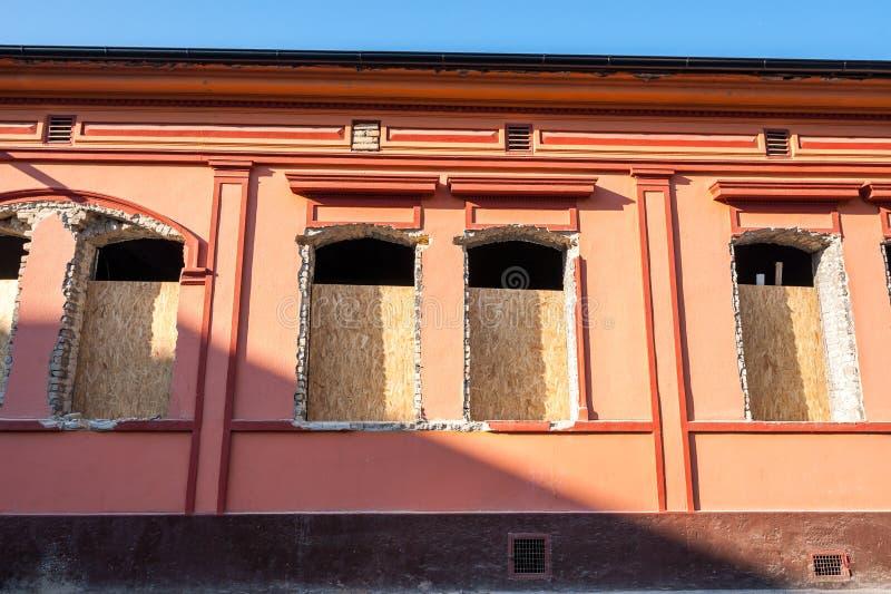 Brutna och skadade fönster med hålet i fasaden av huset eller byggnaden som väntar för att bytas ut stängt och säkrat med trä royaltyfria foton
