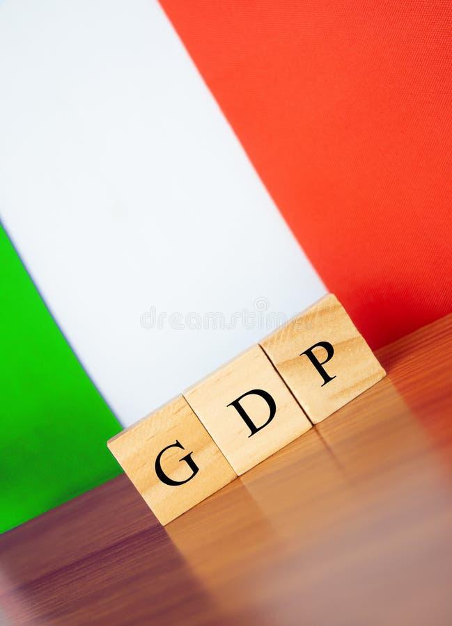 Brutobinnenlands product of het BBP van Italië in houten blokletters op lijst, de vlag van Italië als achtergrond stock afbeeldingen