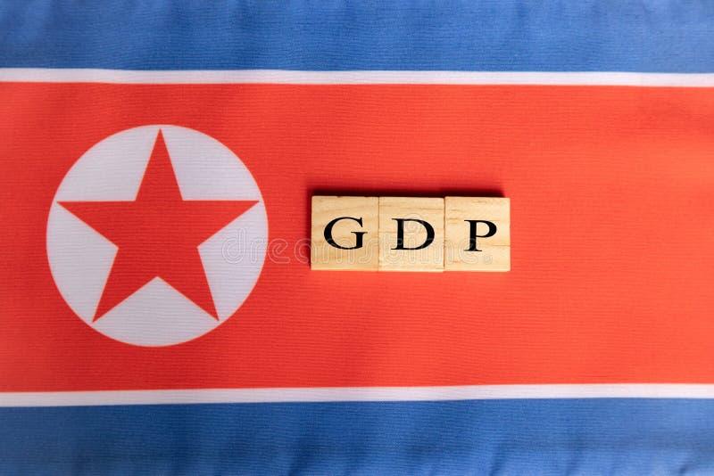 Bruttonationalprodukt eller BNP av Nordkorea i träkvarterbokstäver på nordkoreansk flagga royaltyfri foto